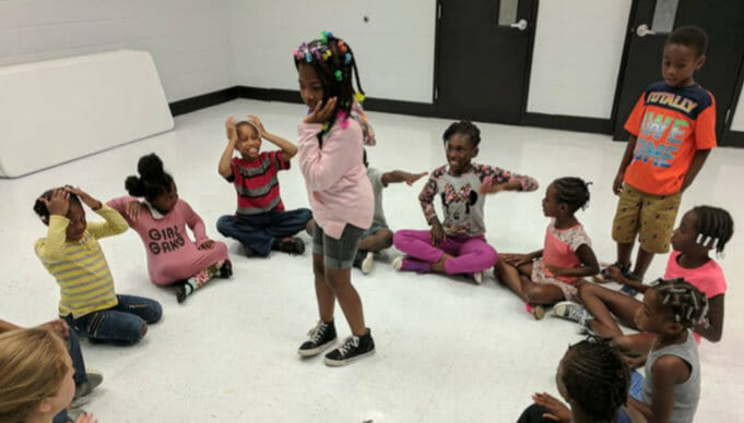 elementary-aged children sit in a circle on the ground during a drama game