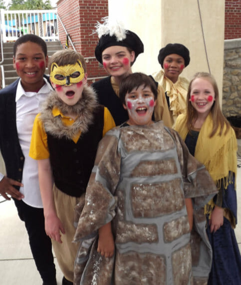 six members of The Bardlings pose in costume backstage at the Cascades Park amphitheater